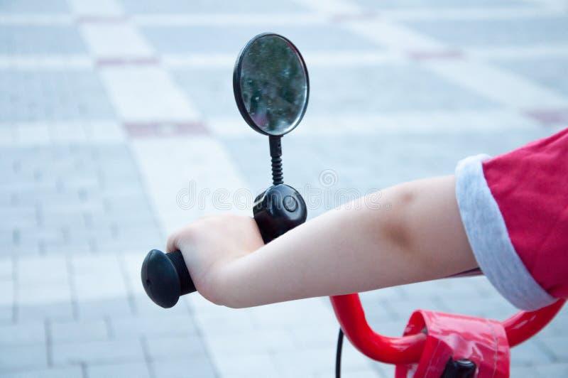 Chłopiec chwytów ręka na bicyklu Lustro na kierownicie W parku zdjęcie stock