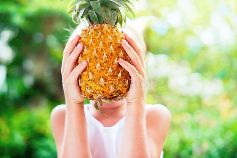 Chłopiec chwyta ananas Wręcza lata tło obrazy stock