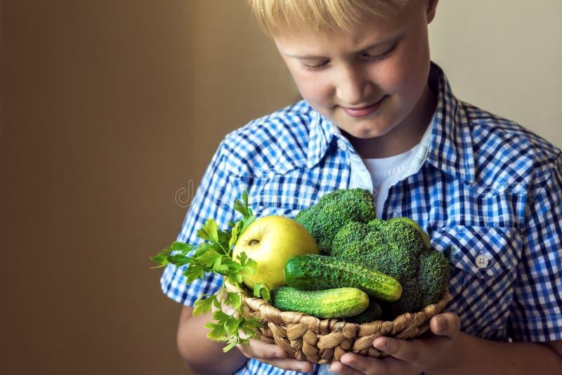 Chłopiec chwyta kosz z zielonymi warzywami zdjęcie royalty free