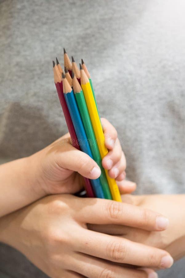 Chłopiec ciągnienie i wyborów kolorowi ołówki od macierzystej ręki obrazy stock