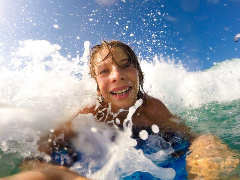 Chłopiec cieszy się jadący fala z surfboard obrazy stock