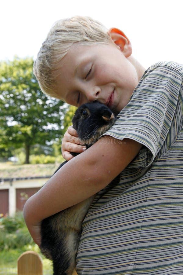 Chłopiec cuddling up z zwierzę domowe królikiem fotografia royalty free