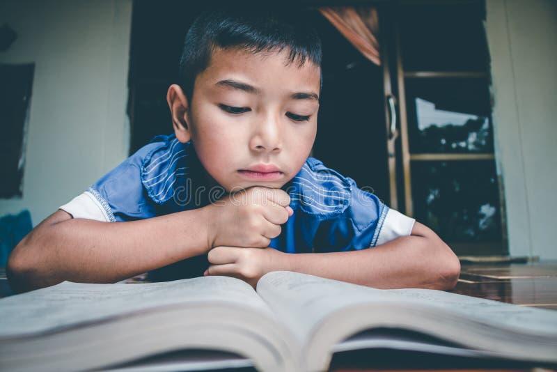 Chłopiec czyta książkę dla przygotowywa egzamin na ten nadchodzącym Poniedziałku zdjęcie royalty free