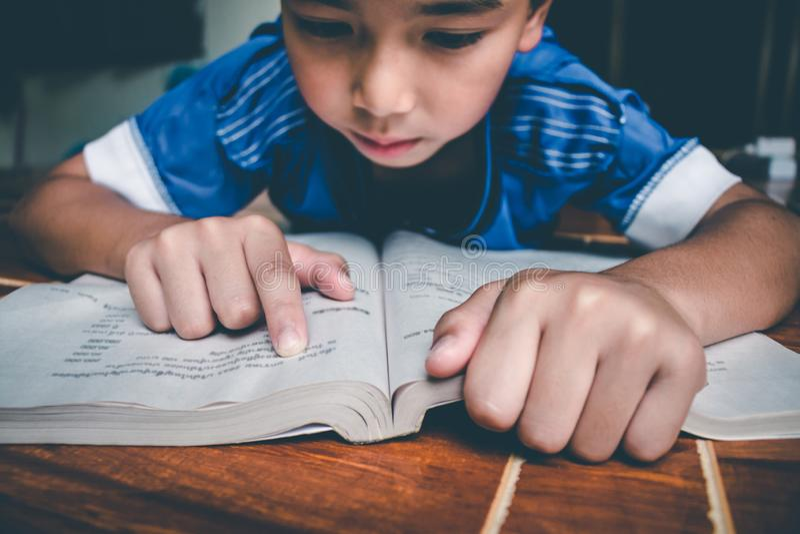 Chłopiec czyta książkę dla przygotowywa egzamin na ten nadchodzącym Poniedziałku obrazy royalty free
