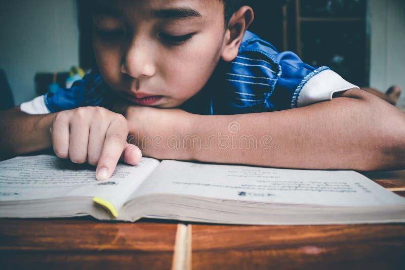Chłopiec czyta książkę dla przygotowywa egzamin na ten nadchodzącym Poniedziałku obraz stock