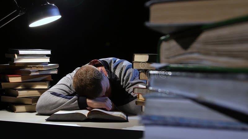 Chłopiec czyta książkę i spada uśpiony na stole Czarny tło zdjęcie wideo