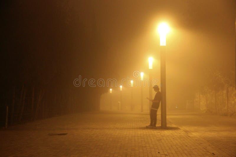 Chłopiec czyta książkę na ulicie pod lampą fotografia stock