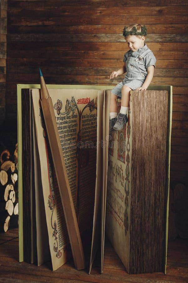 Chłopiec czyta książkę, nauka, wiedza symbol, bibliophile obraz royalty free