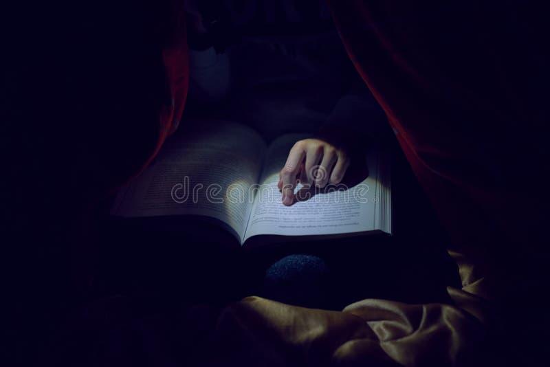 Chłopiec czyta książkę z latarką pod koc obraz royalty free