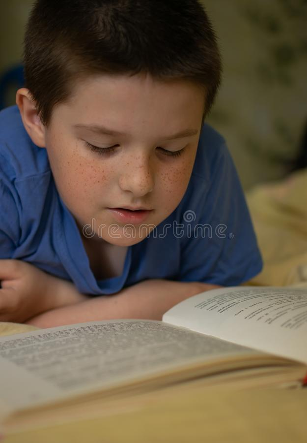Chłopiec czyta książkowego lying on the beach na łóżku obraz royalty free