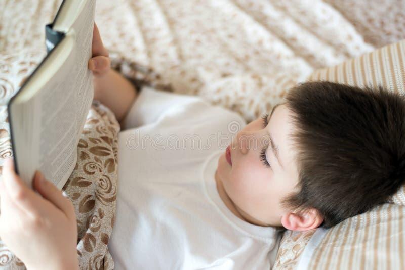 Chłopiec czytelnicza książka przy pora snu lying on the beach w łóżku fotografia stock