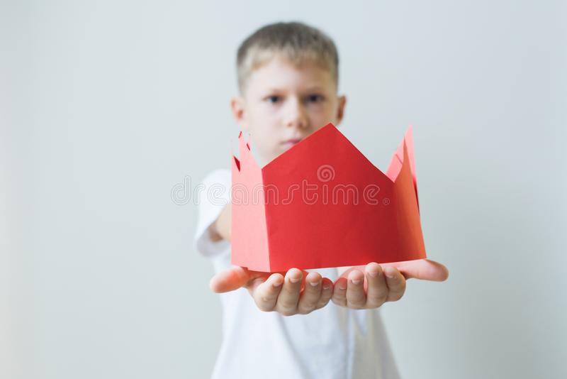 Chłopiec daje czerwonej imitacja papieru koronie Dawać pozycjom obrazy stock