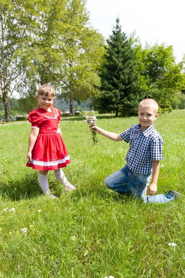 Chłopiec daje kwiatu dziewczyna dzieciak sztuka outdoors zdjęcia royalty free