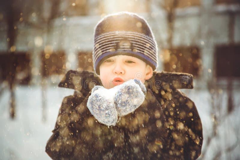 Chłopiec dmucha śnieg z mitynkami na bokeh tle snowfl zdjęcie stock