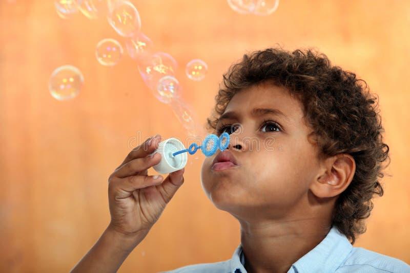 Chłopiec dmucha mydlanych bąble obrazy stock
