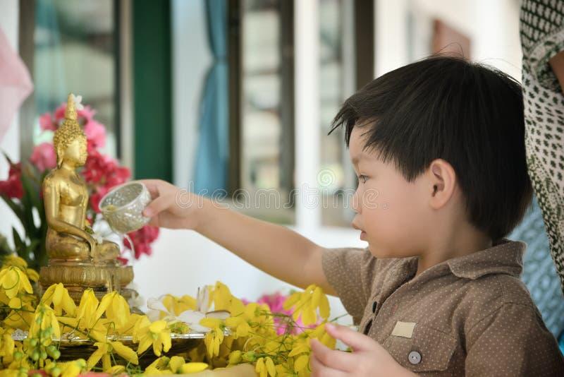 Chłopiec dolewania woda nad Buddha statuą w songkran festiwalu zdjęcie royalty free