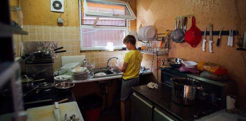 Chłopiec domycia naczynia w kuchni w żółtej koszulce zdjęcie stock