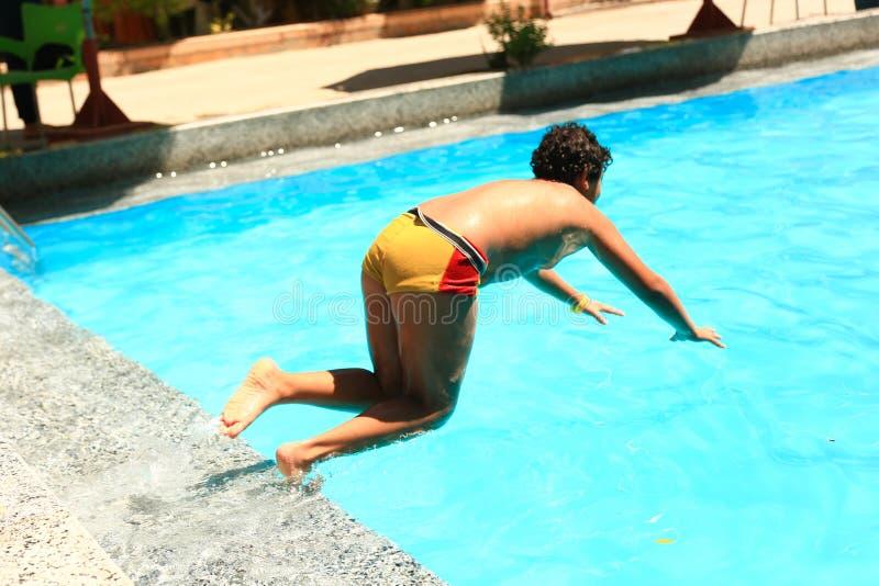 Chłopiec dopłynięcie przy basenem fotografia stock