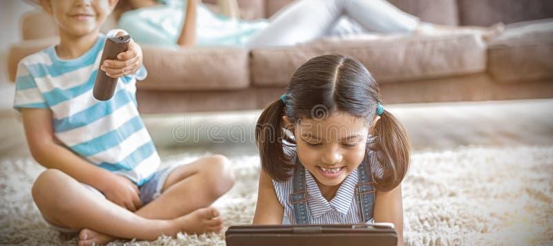 Chłopiec dopatrywania dziewczyna używa cyfrową pastylkę w żywym pokoju i telewizja zdjęcie stock