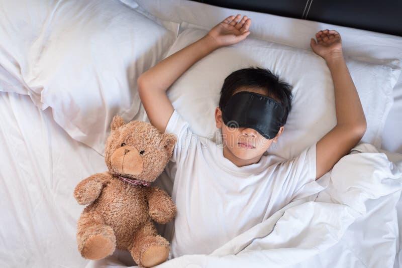 Chłopiec dosypianie na łóżku z miś białą poduszką jest ubranym sen maskę prześcieradłami i zdjęcia royalty free