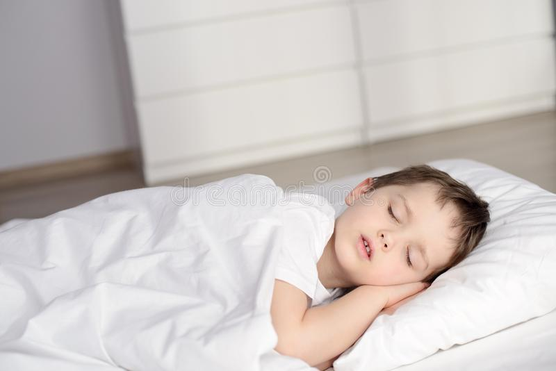 Chłopiec dosypianie w łóżku, szczęśliwy pora snu w białej sypialni zdjęcia stock