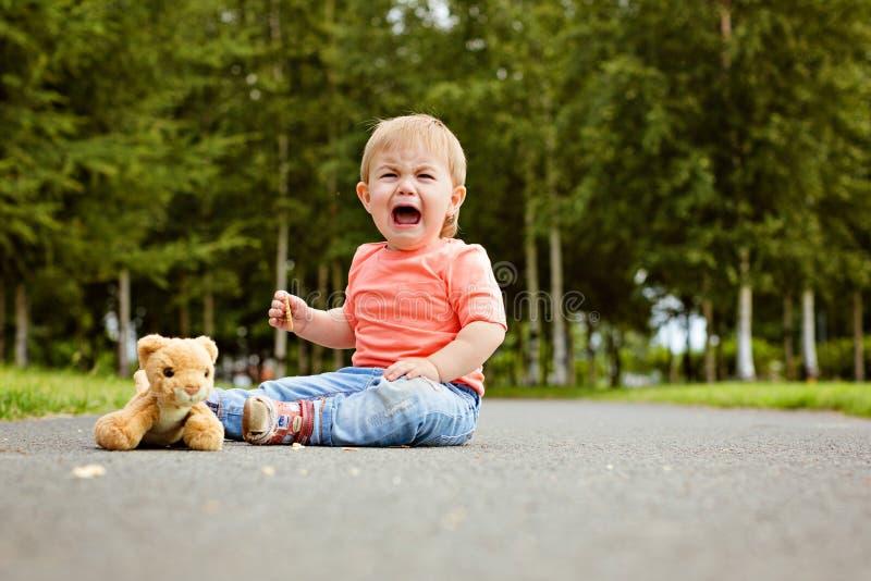 Chłopiec dzieciak w niebieskich dżinsach płacze gorzki, siedzący na zdjęcia royalty free