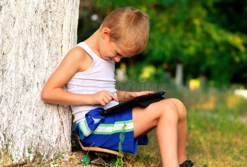 Chłopiec dziecko bawić się z pastylka pecetem Plenerowym obrazy stock