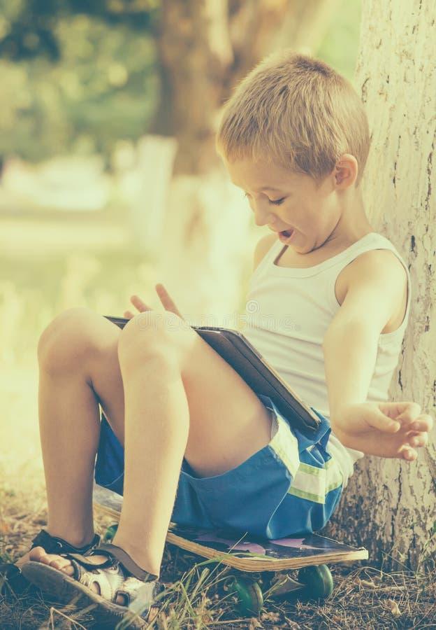 Chłopiec dziecko bawić się z pastylka pecetem Plenerowym zdjęcie stock