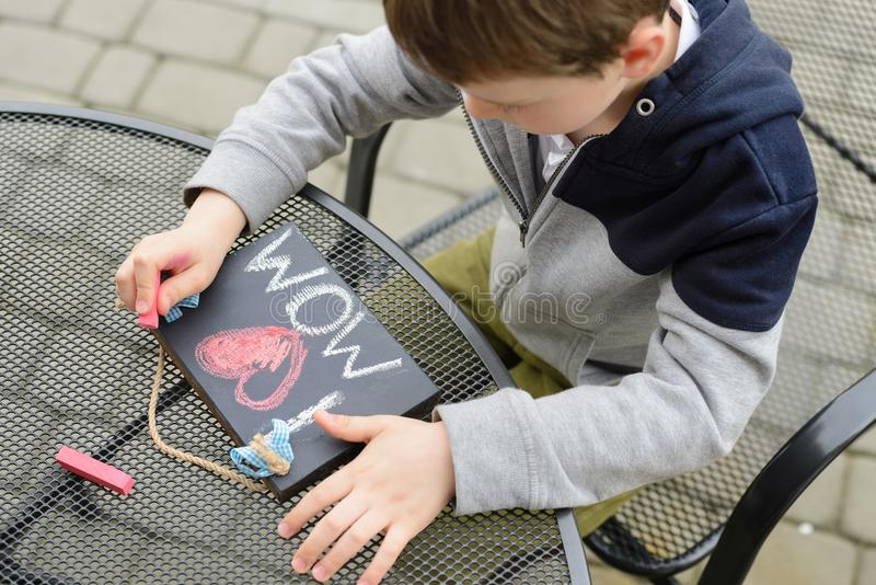 Chłopiec dziecko rysuje miłości deklarację obraz royalty free