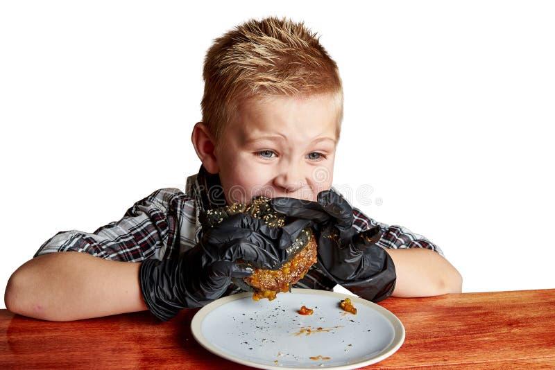 Chłopiec emocjonalnie je hamburger w czarnych rękawiczkach obrazy stock