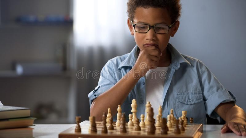 Chłopiec główkowanie na szachowym ruchu, inteligentny hobby, logika rozwój, czas wolny fotografia royalty free