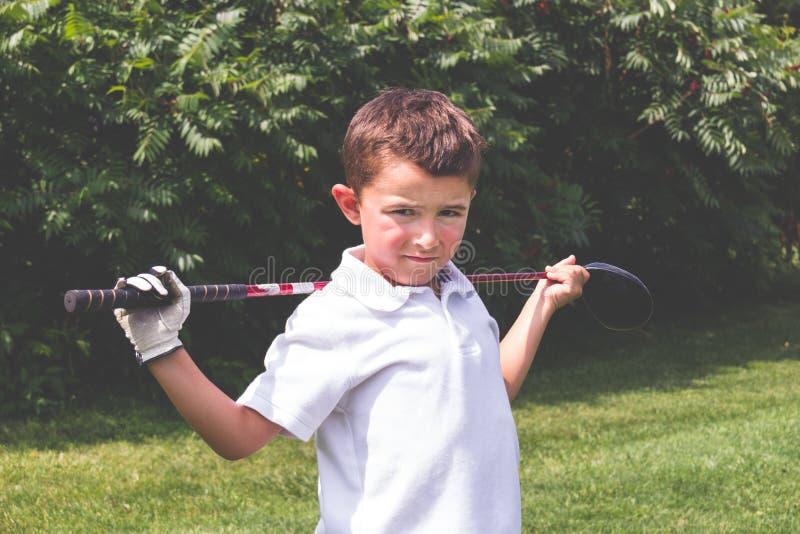 Chłopiec golfista z kierowcy klubem nad ramionami pozuje dla krzywka obrazy stock