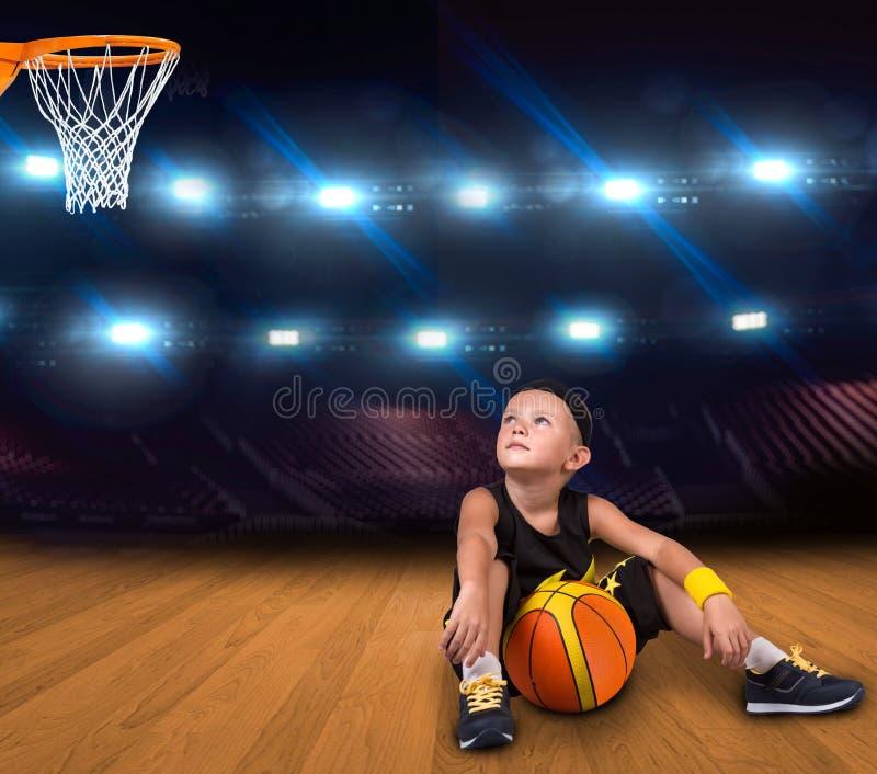 Chłopiec gracz koszykówki z balowym obsiadaniem na podłodze w gym i sen wielkie zwycięstwa obraz royalty free