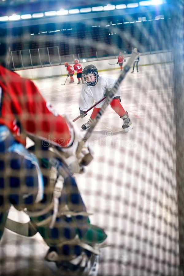 Chłopiec gracz w hokeja strzelają krążek hokojowego i atakują fotografia stock