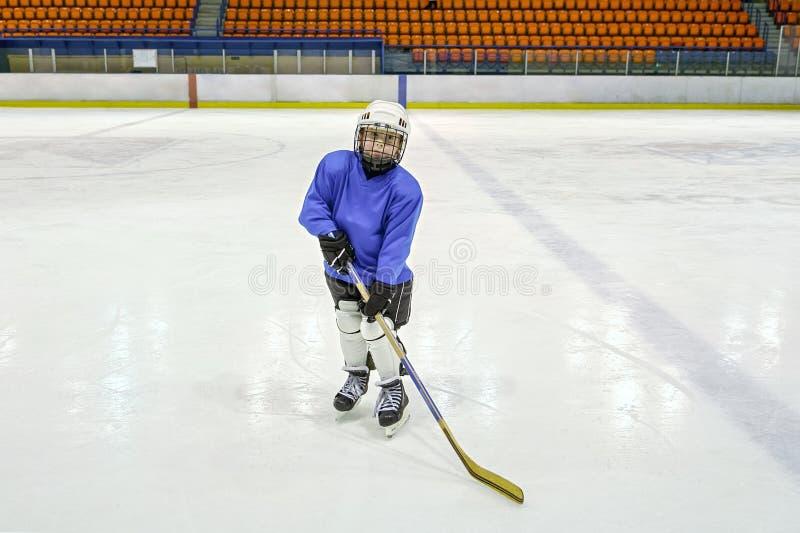Chłopiec gracz w hokeja z pełnym wyposażeniem w blaue unifor i fotografia royalty free