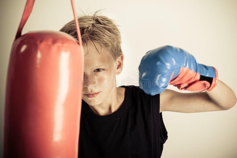 Chłopiec huśtawki przerzedżą gloved rękę przy czerwoną uderza pięścią torbą obrazy stock