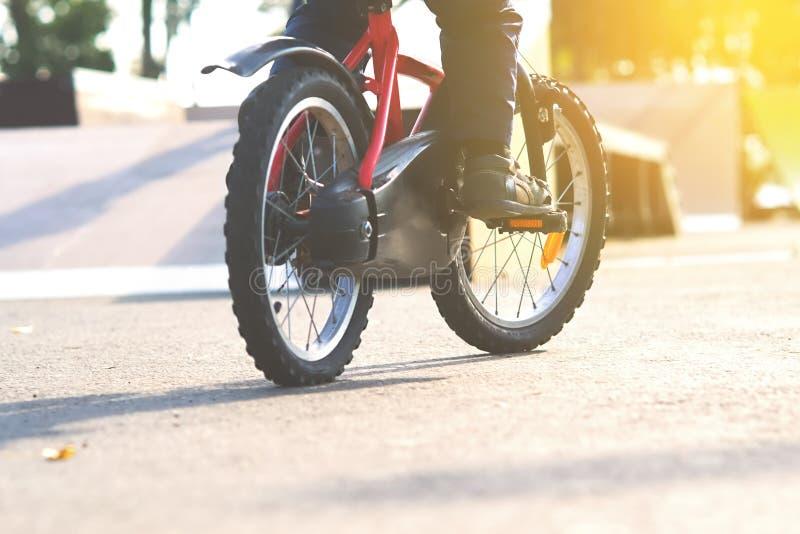 Chłopiec iść wewnątrz dla sportów na bicyklu i uczy się jechać w, jeździć na łyżwach parka opuszcza skłon w słońcu przy zmierzche fotografia royalty free