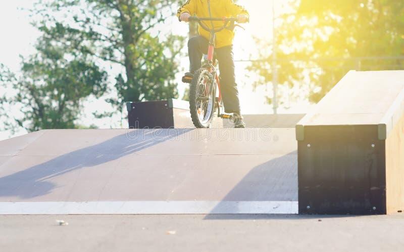Chłopiec iść wewnątrz dla sportów na bicyklu i uczy się jechać w, jeździć na łyżwach parka opuszcza skłon w słońcu przy zmierzche obrazy stock