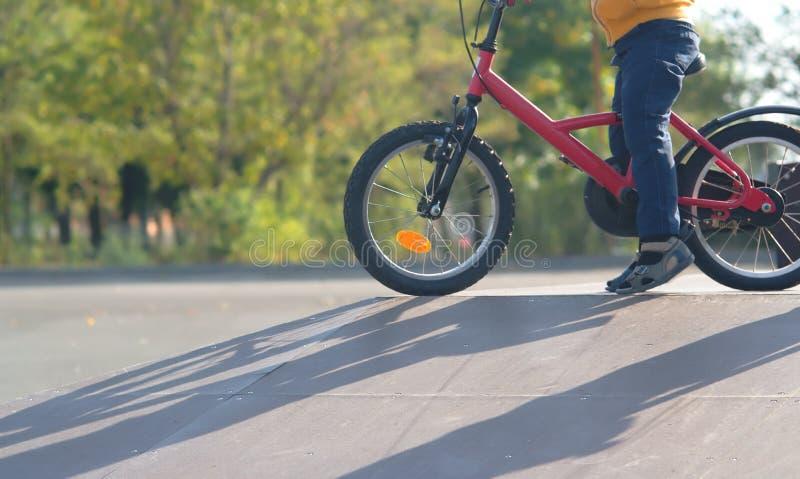 Chłopiec iść wewnątrz dla sportów na bicyklu i uczy się jechać w, jeździć na łyżwach parka opuszcza skłon w słońcu przy zmierzche zdjęcie royalty free