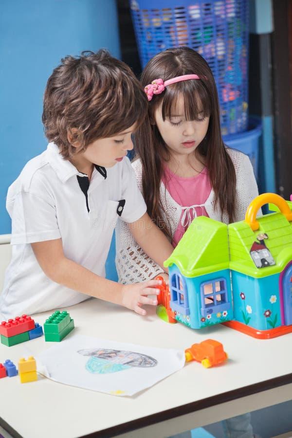Chłopiec I dziewczyna Bawić się Z klingerytu domem Wewnątrz obraz royalty free