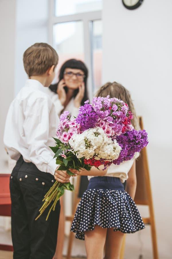 Chłopiec i dziewczyna dajemy kwiaty jako nauczyciel w nauczyciela ` s dniu zdjęcia stock
