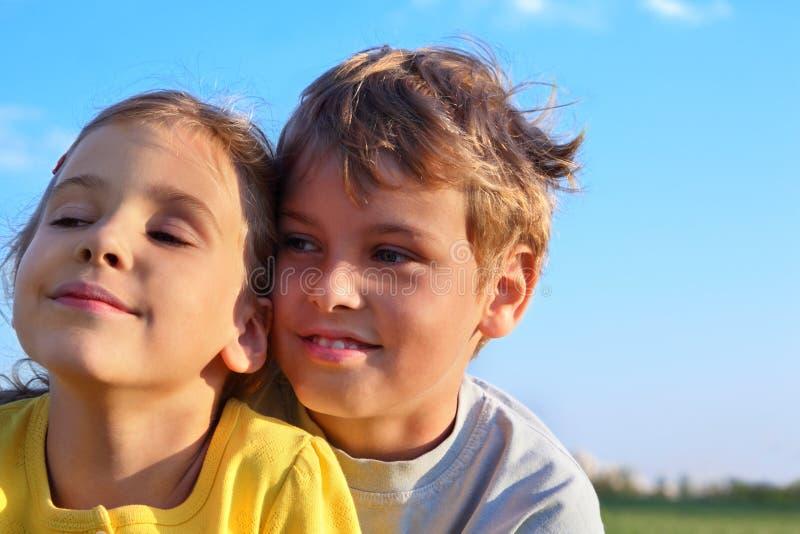 Chłopiec i dziewczyna ja uśmiechamy się i patrzejemy w kierunku zdjęcia stock
