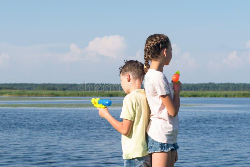 Chłopiec i dziewczyna jesteśmy trwanie z powrotem popierać i mienie wodne krócicy w ich rękach, bawić się w naturze na wakacje fotografia stock