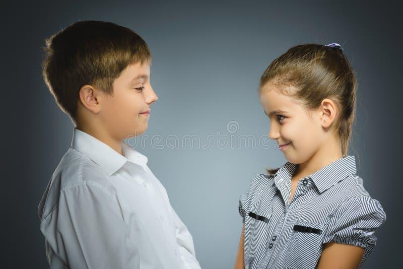 Chłopiec i dziewczyna jesteśmy uśmiechnięci przy each inny Portretów dzieci odizolowywający na popielatym zdjęcia royalty free