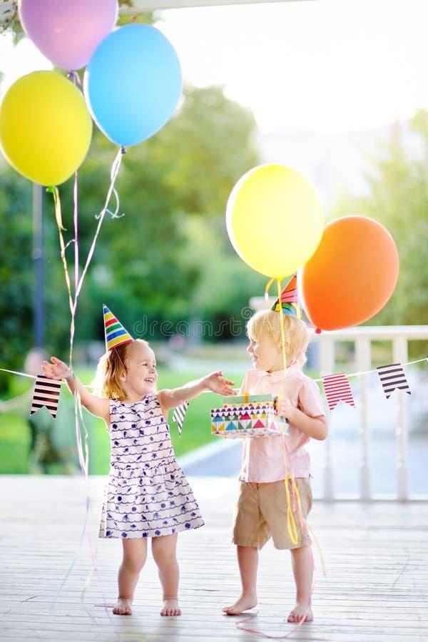 Chłopiec i dziewczyna ma zabawę i świętujemy przyjęcia urodzinowego z kolorowymi balonami zdjęcia royalty free