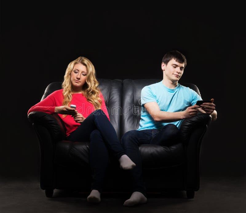 Chłopiec i dziewczyna siedzi oddzielnie z smartphones obraz stock