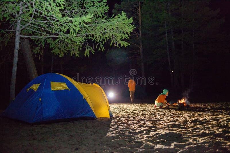 Chłopiec i dziewczyna siedzimy przy noc turystami namiotowymi obraz stock