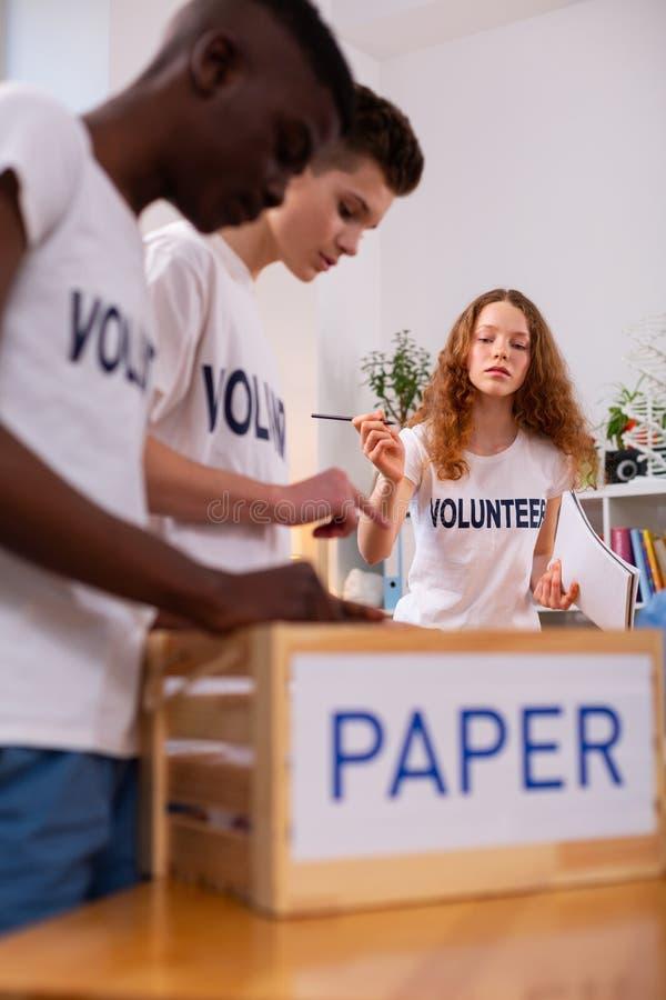 Chłopiec i dziewczyna sortuje papier podczas gdy pracujący w ekologii organizacji zdjęcie royalty free