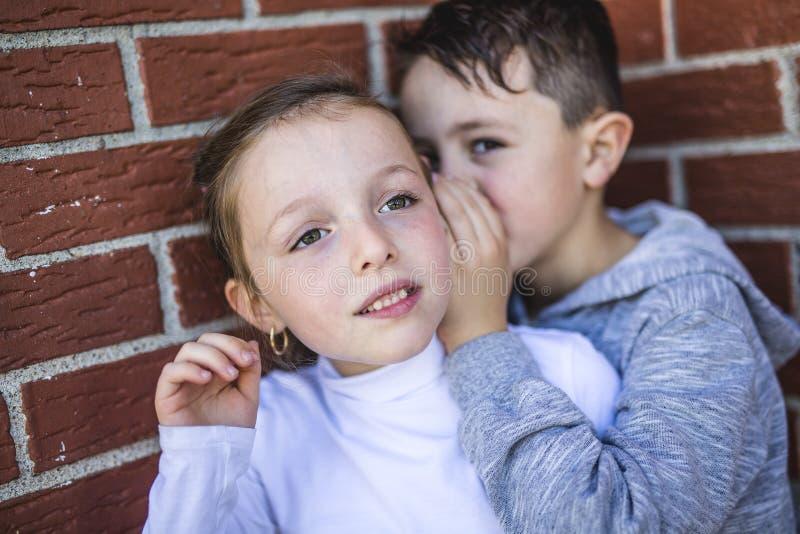 Chłopiec i dziewczyna szepczemy sekret zdjęcia stock