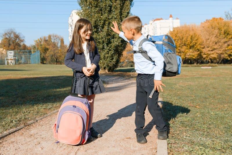 Chłopiec i dziewczyna, szkoła podstawowa ucznie z plecakami iść szkoła Słonecznego dnia tło, droga w parku zdjęcie royalty free